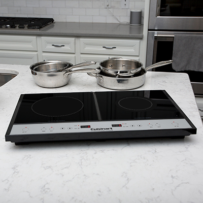 CUISINART <sup>®</sup> Double Induction Cooktop - Two burner induction cooktop heats up faster and uses 70% less energy than conventional cooktops. Left burner has 8 heat settings and right burner offers 5 heat settings.  Sleek glass top design and bright LED timer display. Heat automatically stops 30 seconds after pot or pan is removed from burner.